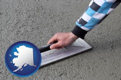 alaska map icon and a masonry contractor using a trowel